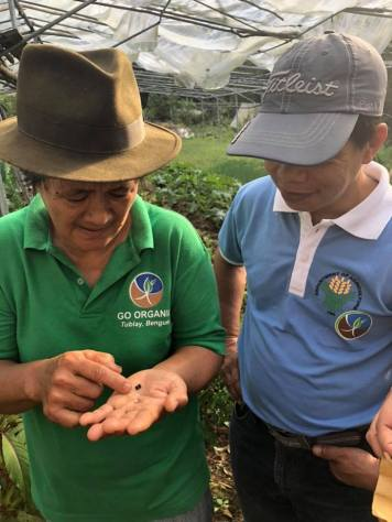 BASS Farmers Mary and Pastor Jun looking at seeds.